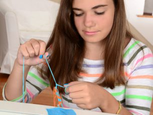 A pretty girl macrames a colorful friendship bracelet using blue and orange thread.